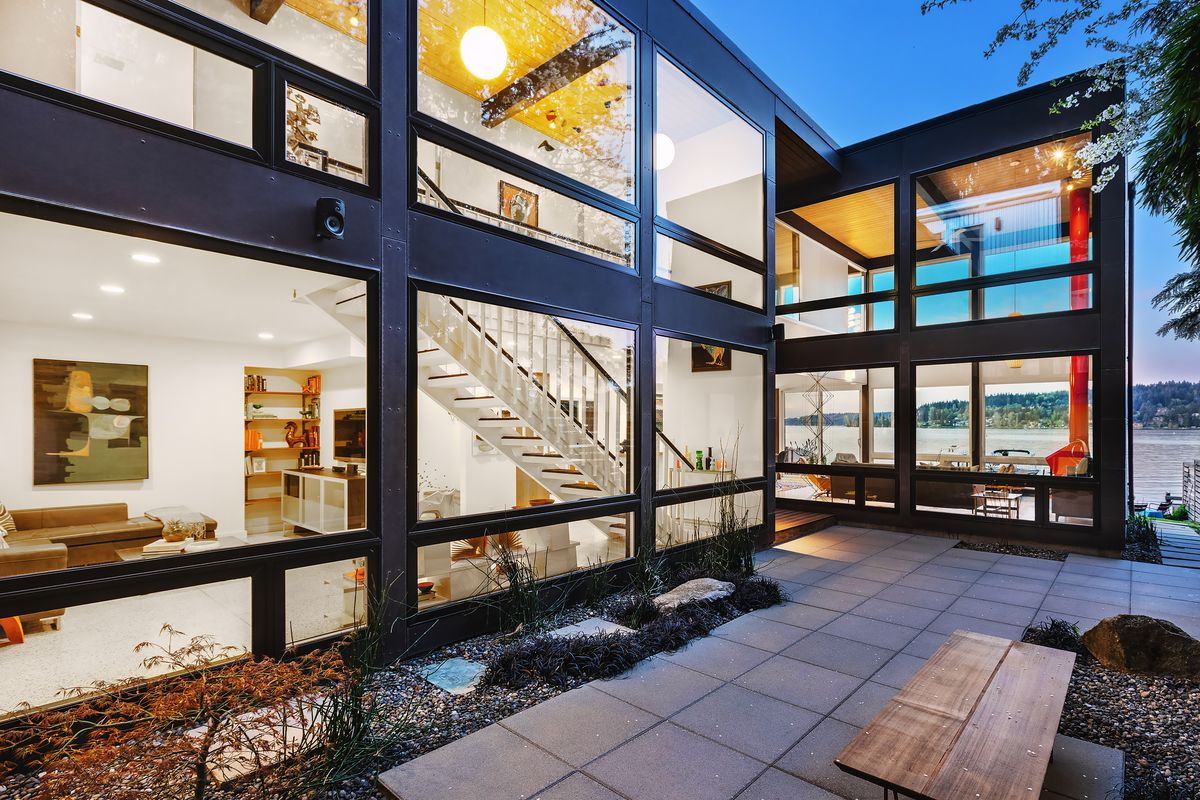 An exterior view of a glass and steel house with a courtyard. The home's lights are on so you can see inside.