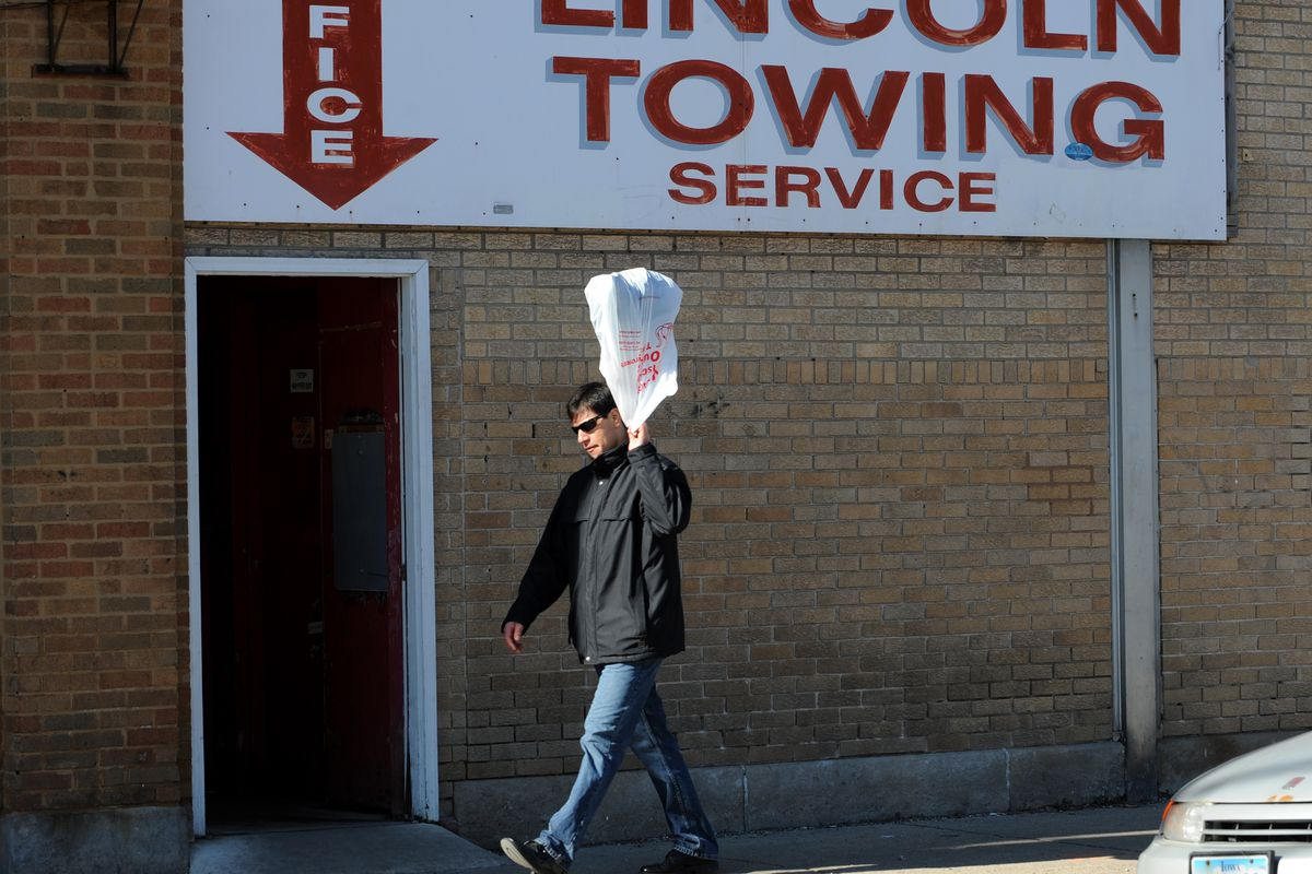A man swings a plastic bag over his shoulder while walking past Lincoln Towing Service in 2009.