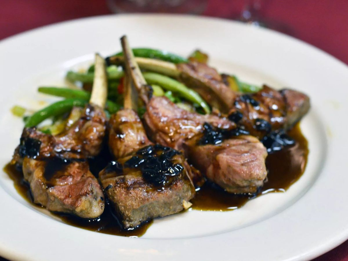 A plate of lamb chops is topped with a dark chutney and served with green beans
