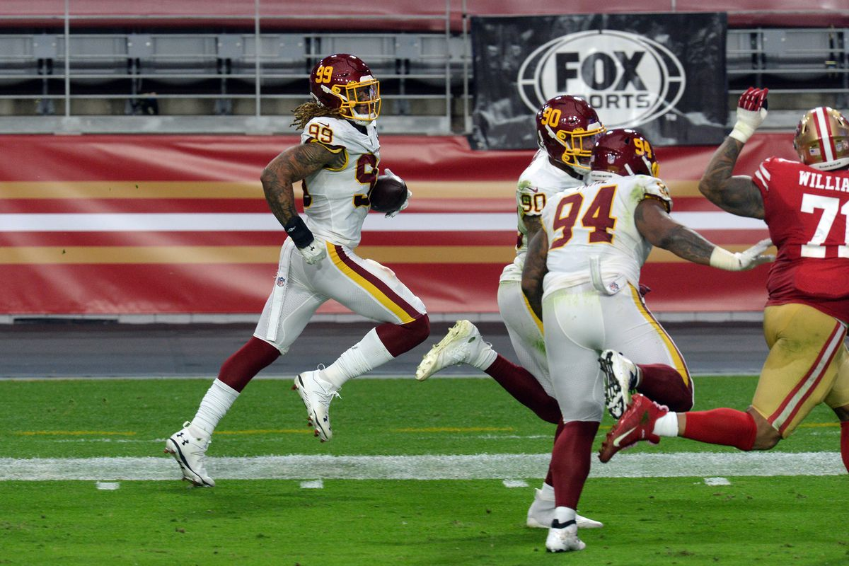 Washington Football Team defensive end Chase Young (99) returns a fumble for a touchdown against the San Francisco 49ers during the first half at State Farm Stadium.