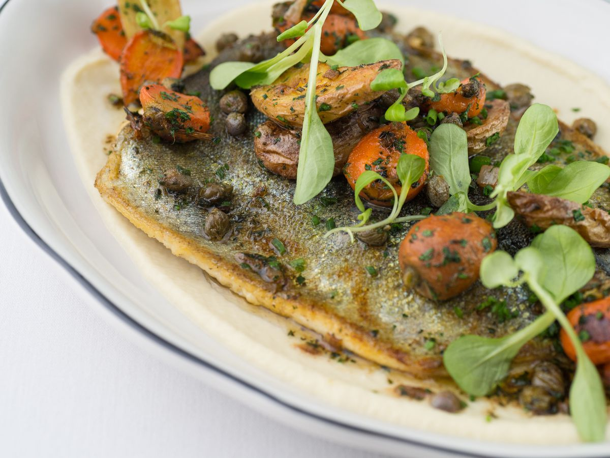 A seared piece of trout topped with charred cherry tomatoes and watercress