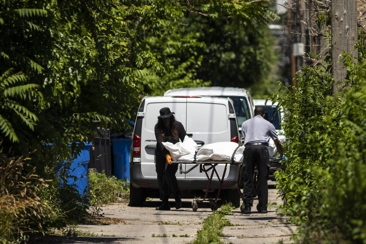A crew removes one of four bodies from a house in the 6200 block of South Morgan after they were all shot to death when an argument broke inside the Englewood building, Tuesday afternoon, June 15, 2021. Four other people were wounded in the shooting.