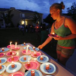 Sage Watson grabs a candle as friends gather during a candlelight vigil in Logan Thursday, July 10, 2014. Ronald Lee Haskell, a recent Logan resident, has been charged with multiple counts of capital murder in a shooting in Texas. Haskell and his family lived in Logan for several years.