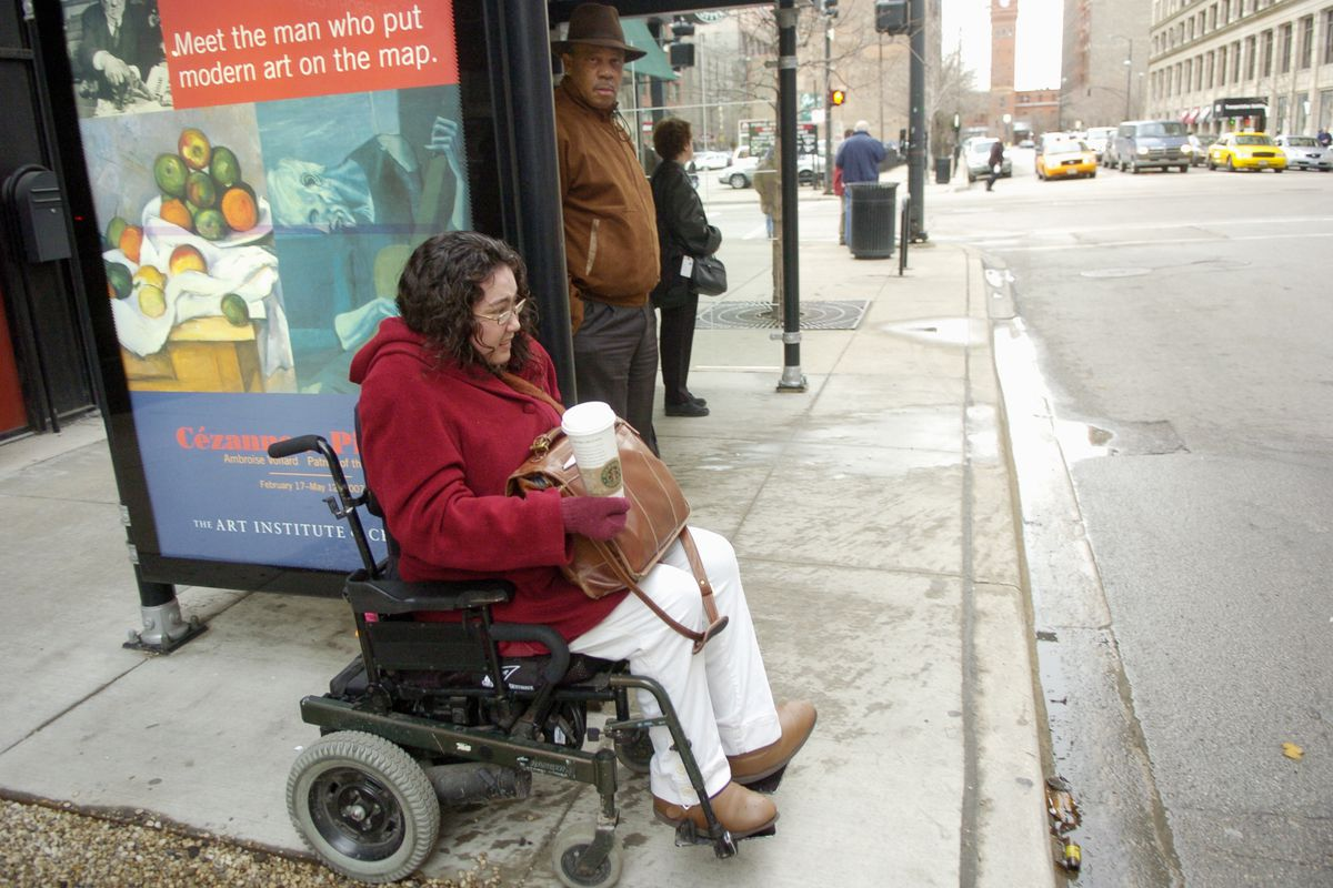A woman using a wheelchair waits for a bus at the corner of Dearborn and Harrison in Chicago.
