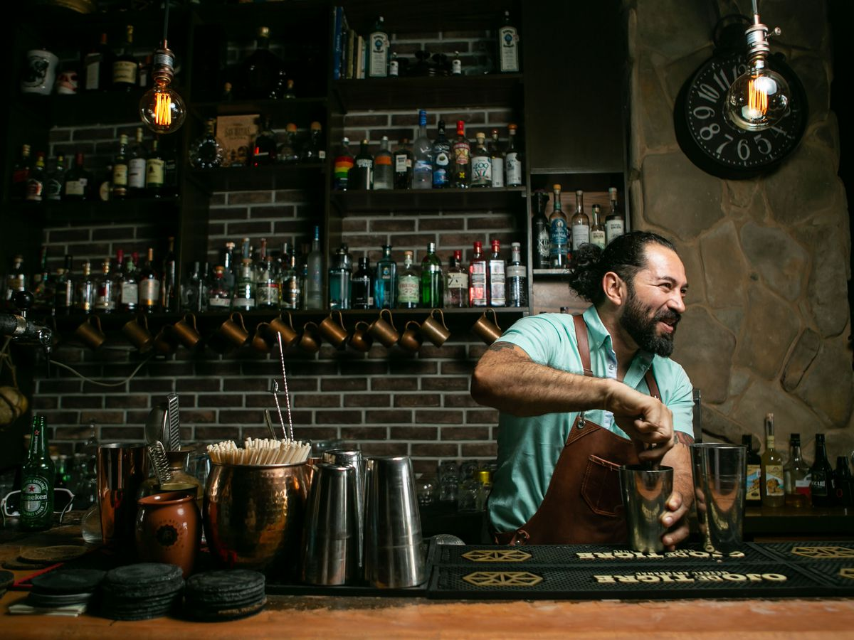 A smiling bearded man mixes a cocktail behind a bar.