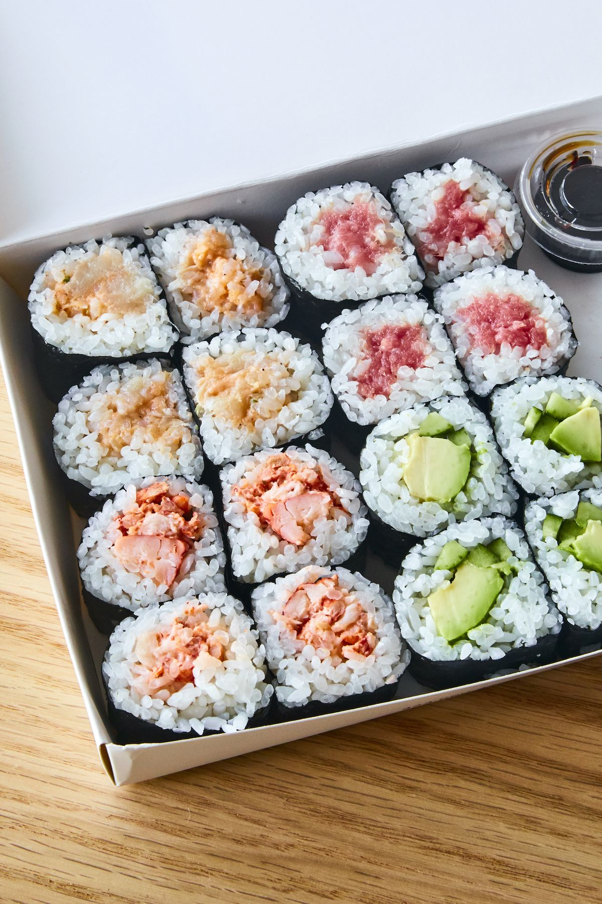 A colorful sushi takeout box with rolls lined up.