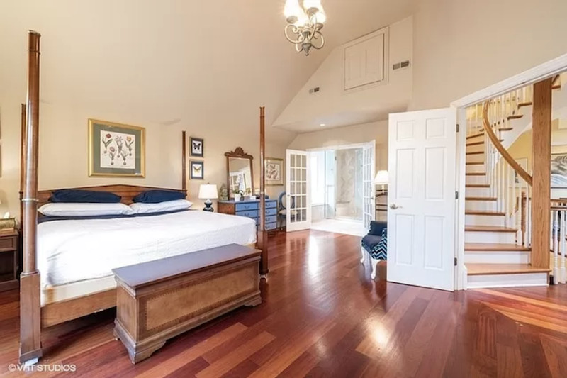 A master bedroom with hardwood floors, an attached bathroom, and a four-post bed.