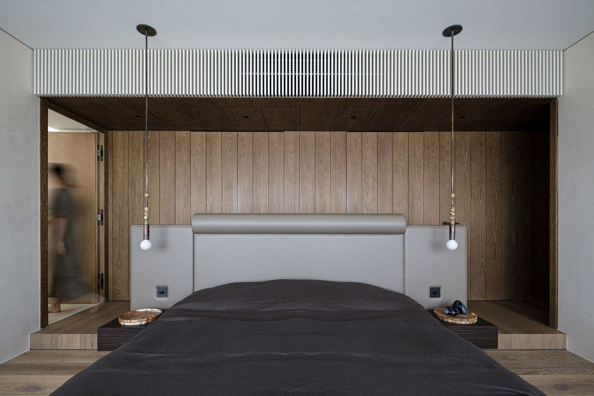 Bedroom with timber backdrop and gray bedding.