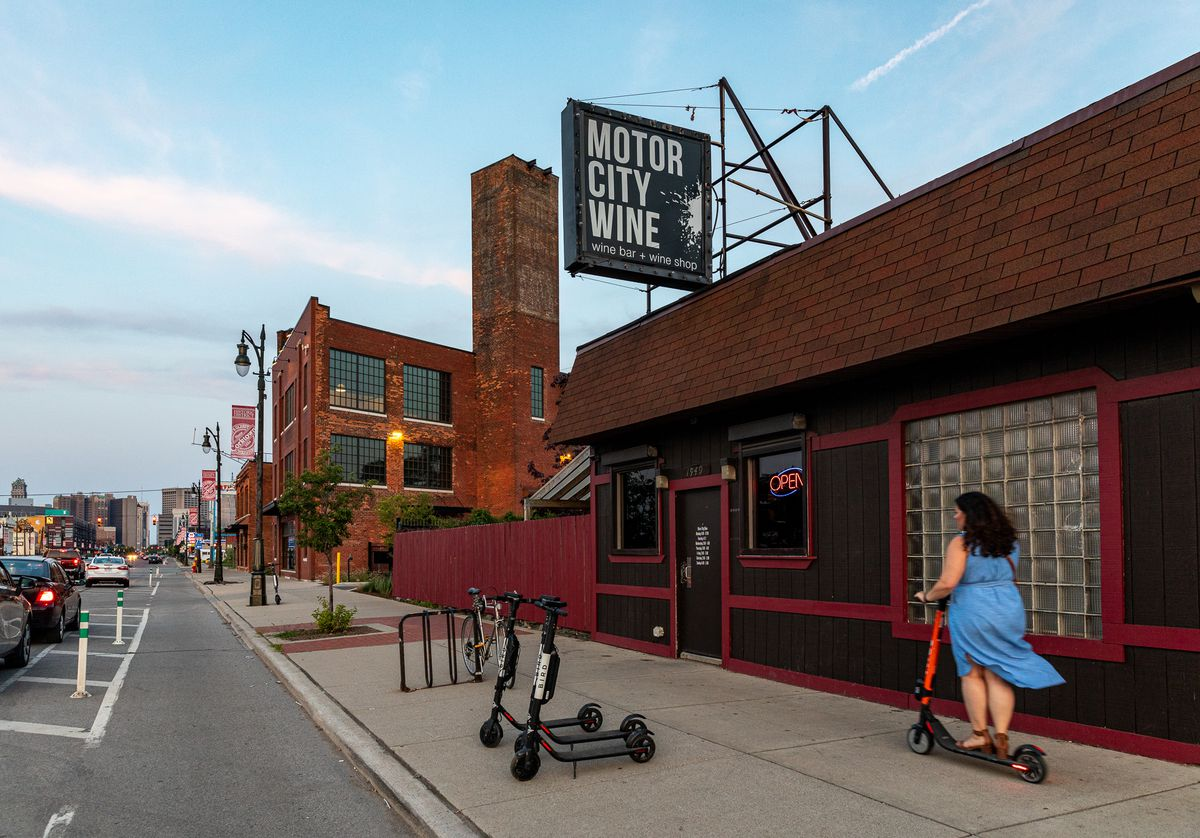 a woman rides by on a red scooter in a blue dress in front of motor city wine. the bar has a dark brown and red facade.