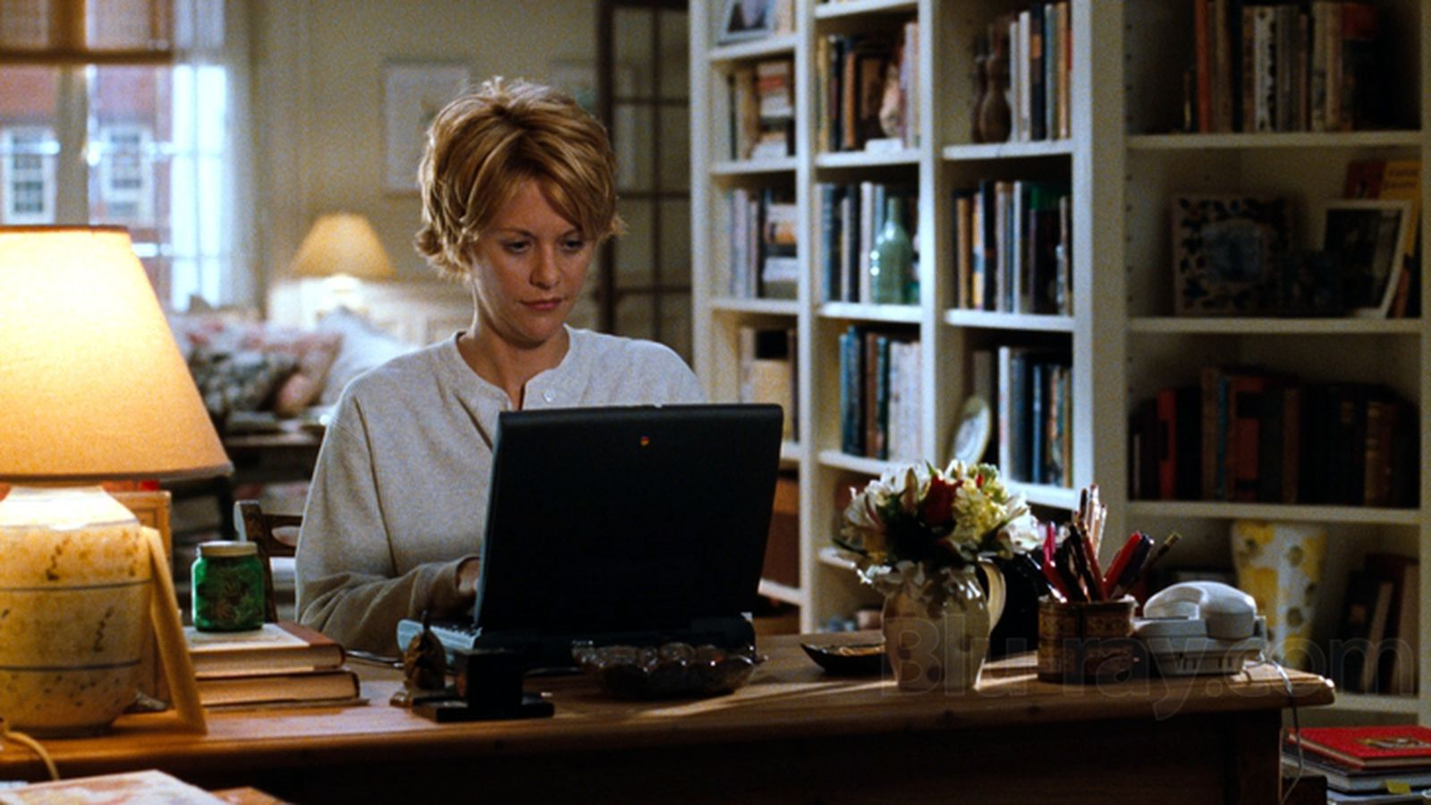 Meg Ryan in You've Got Mail. Kathleen types at her laptop in her home. She looks curious.