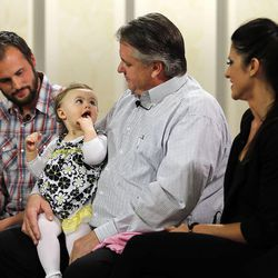 Chad Groesbeck holds his granddaughter, Lily Groesbeck, during an interview in Salt Lake City, Monday, March 16, 2015. The 18-month-old survived 14 hours trapped in a car upside down in the Spanish Fork River. At left is Garrett Groesbeck, Lily's uncle. At right is Jill Sanderson, Lily's aunt.
