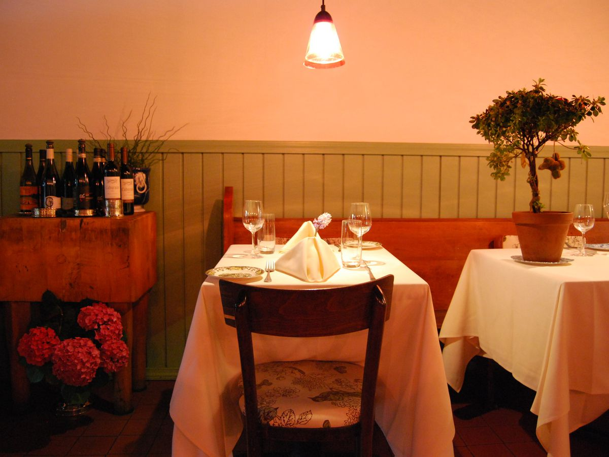 Warm lighting covers a dining area with green wood paneling on one half of a wall, a two-seat table covered in a white tablecloth, and a small bar stand with wine bottles