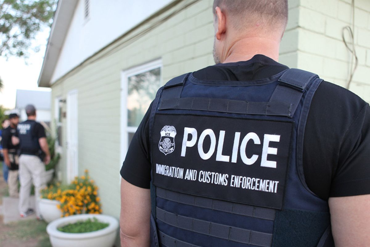 closeup of ICE officer's back, blurry arrestees in background, outside a house