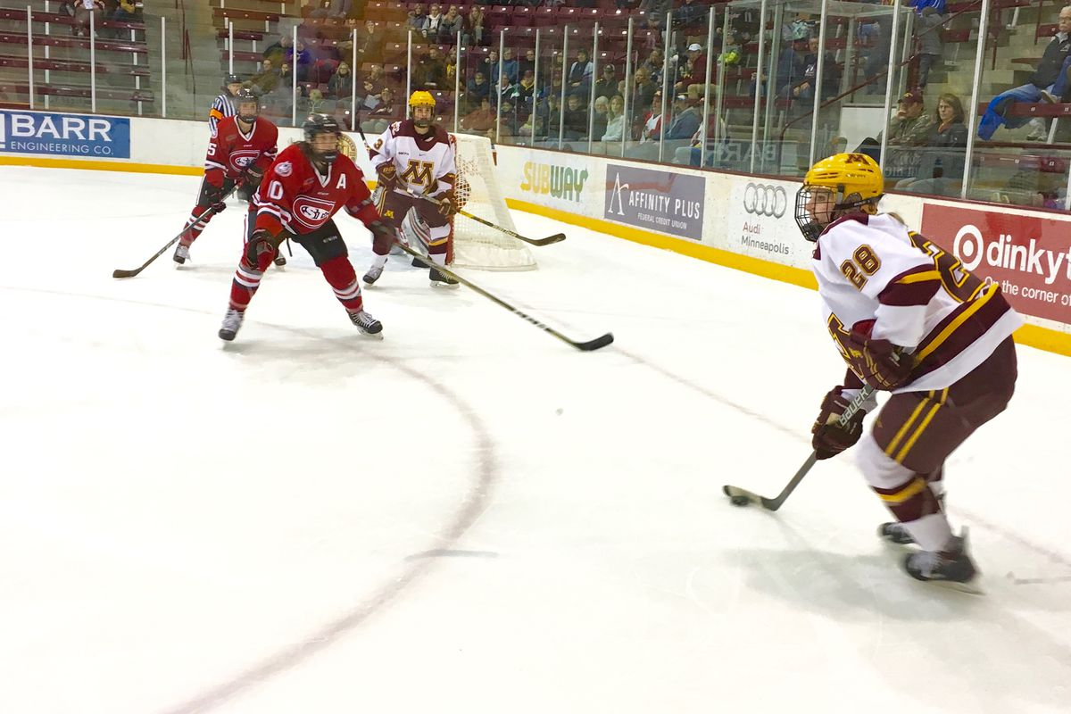 Taylor Wente trying to get past some St. Cloud players without losing the puck.