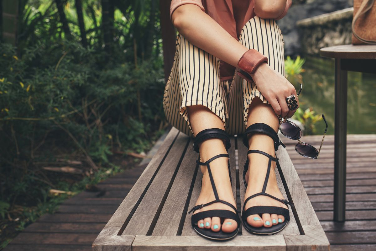 A woman sitting on a bench wearing black sandals
