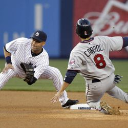 New York Yankees shortstop Derek Jeter, left, gets the ball in time to prevent Minnesota Twins' Jamey Carroll from stealing second during the first inning of a baseball game at Yankee Stadium in New York, Monday, April 16, 2012.