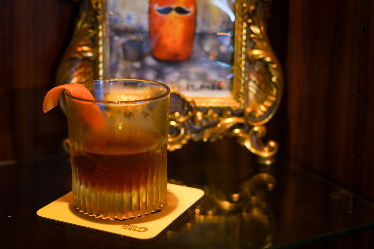 A closeup of a brown cocktail in a foggy glass with an orange peel garnish and a mirror in the background displaying a floating mustache