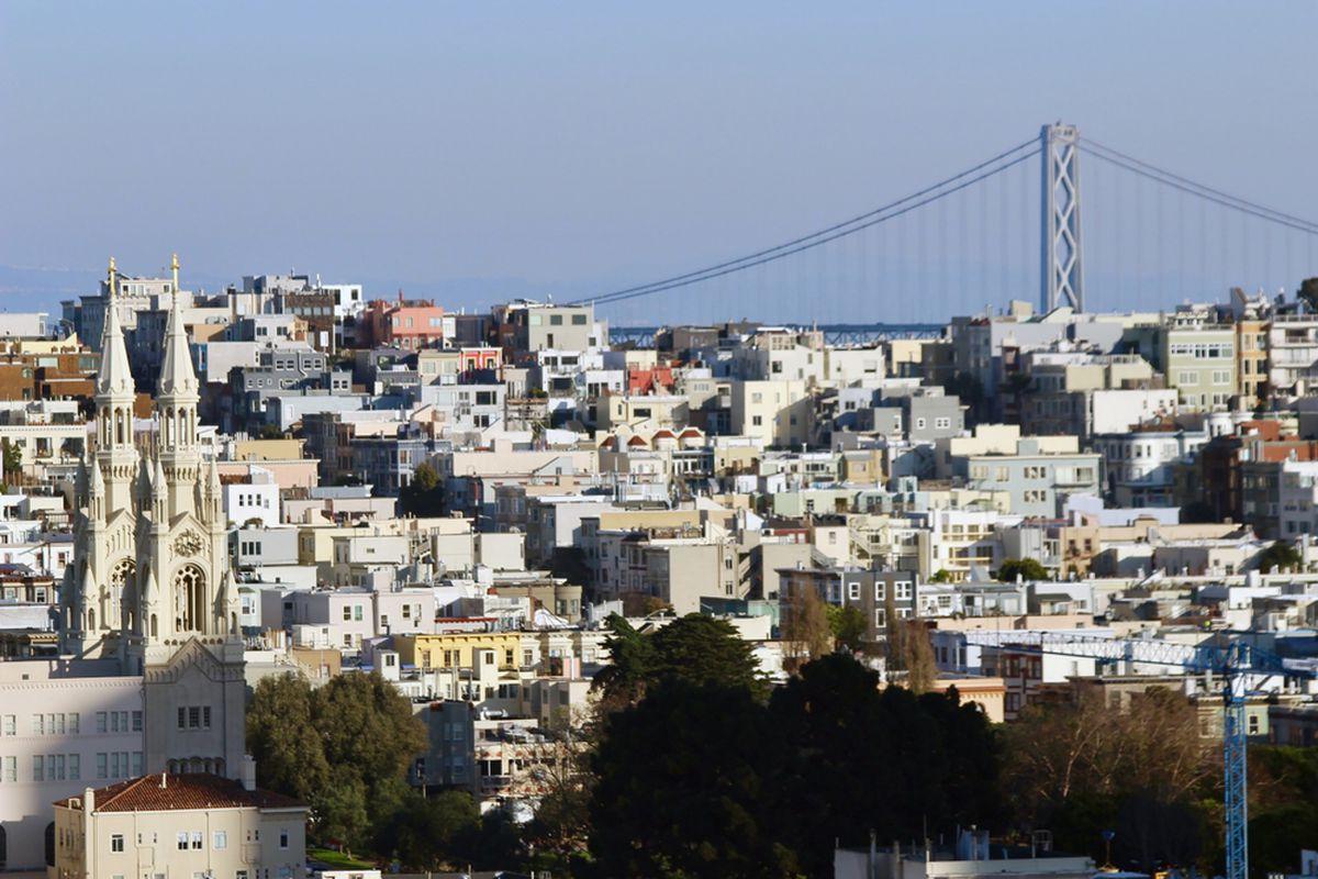 The San Francisco Bay Bridge behind rows of houses.