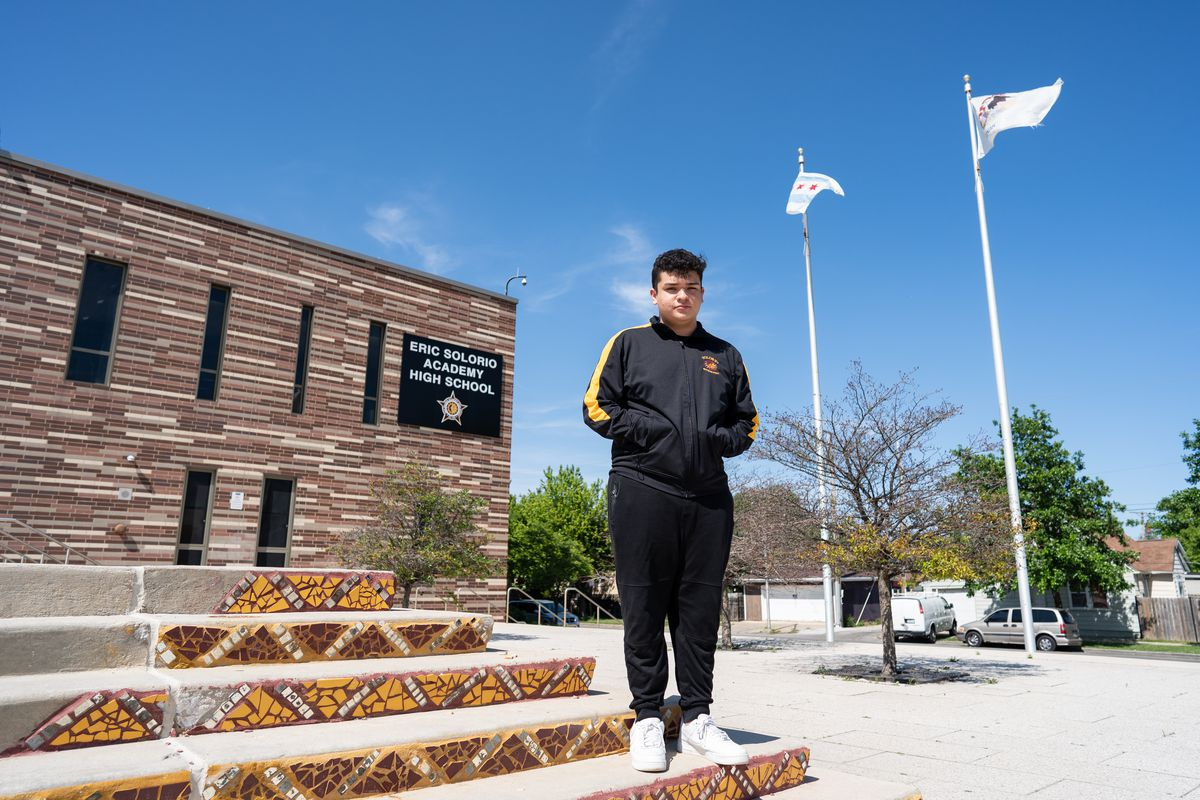 A young man wearing a black and yellow track jacket and white sneakers stands in front of Eric Solorio Academy High School.