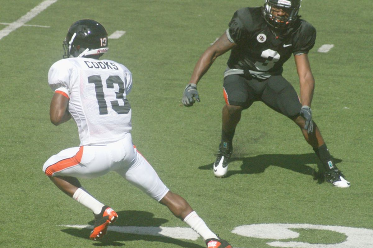 Brandin Cooks grabs a pass and cuts past safety Anthony Watkins in Oregon St.'s scrimmage Tuesday afternoon. <em>(Photo by Andy Wooldridge)</em>