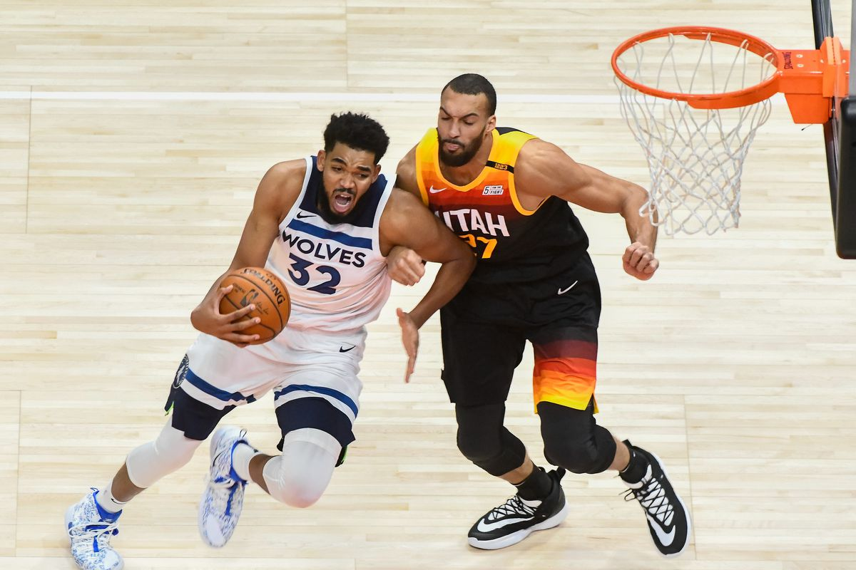 Karl-Anthony Towns of the Minnesota Timberwolves drives against Rudy Gobert of the Utah Jazz during a game at Vivint Smart Home Arena on December 26, 2020 in Salt Lake City, Utah.