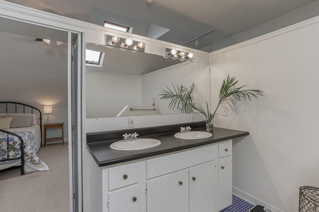 A white bathroom space with a dated vanity.
