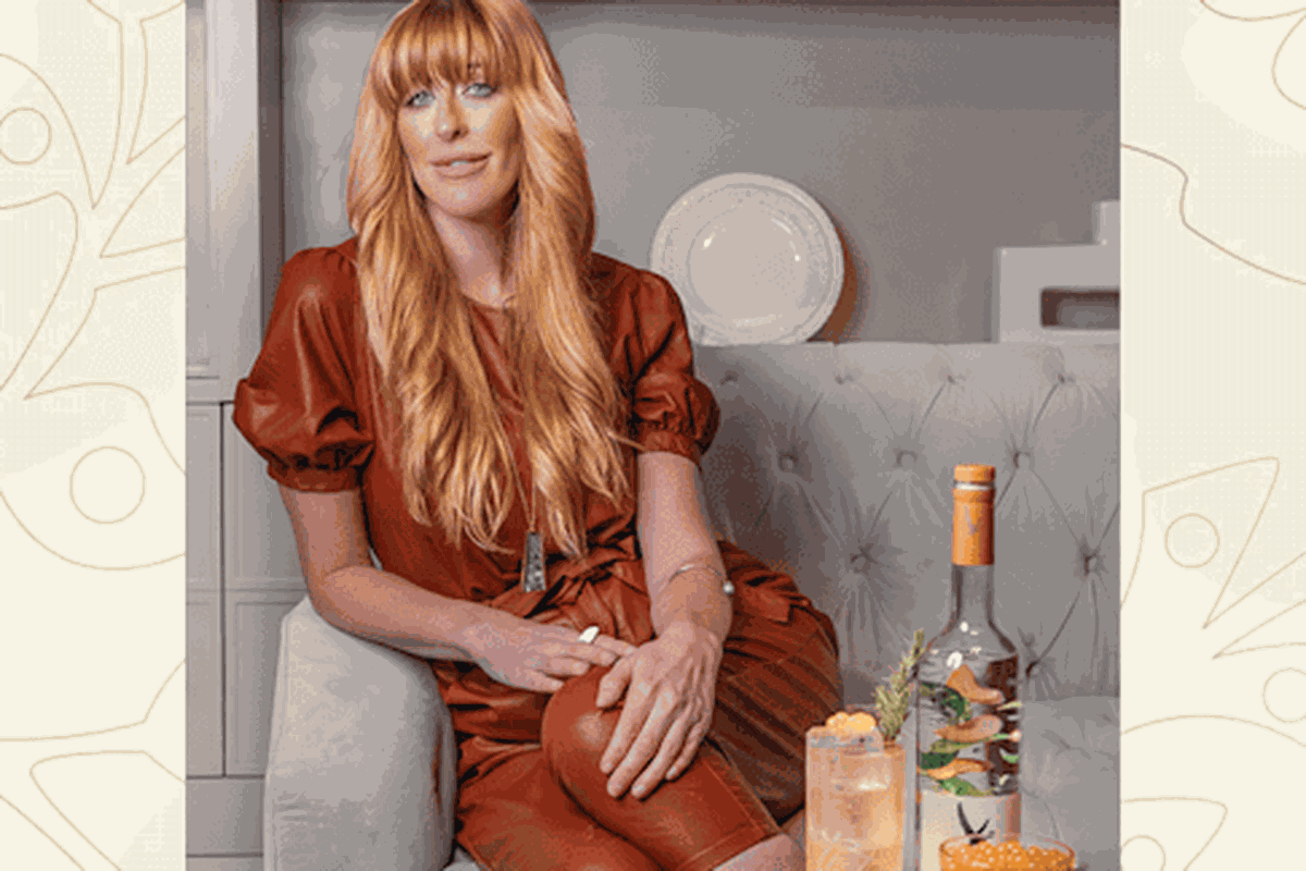 A woman with long blond hair wears a brown leather outfit sitting on a couch