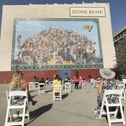 """Guests listen to a speaker during the unveiling of the """"Utah Women 2020"""" mural on the Dinwoodey Building in Salt Lake City on Wednesday, Aug. 26, 2020.The mural, commissioned by Zions Bank in honor of women's suffrage, depicts images of 250 Utah women past and present."""