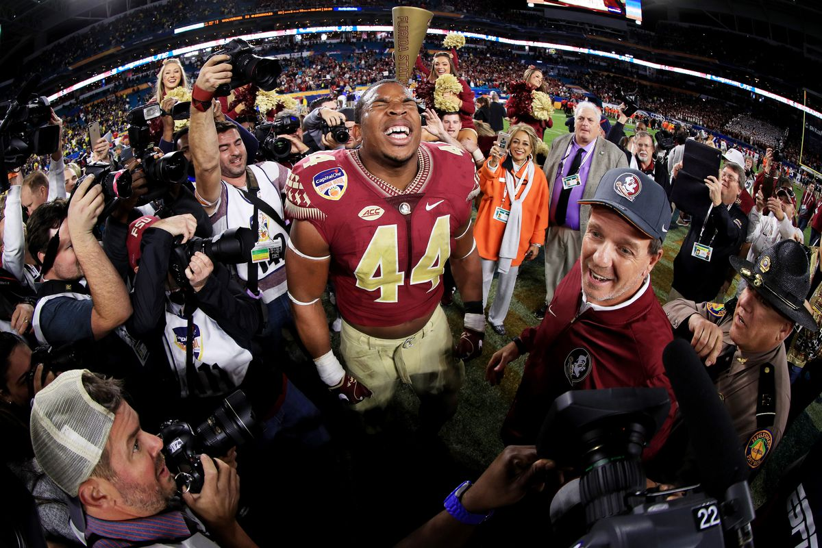 MIAMI GARDENS, FL - Florida State Seminoles defensive end DeMarcus Walker (44) and head coach Jimbo Fisher celebrate their 33-32 victory over the Michigan Wolverines during the Capitol One Orange Bowl at Sun Life Stadium.