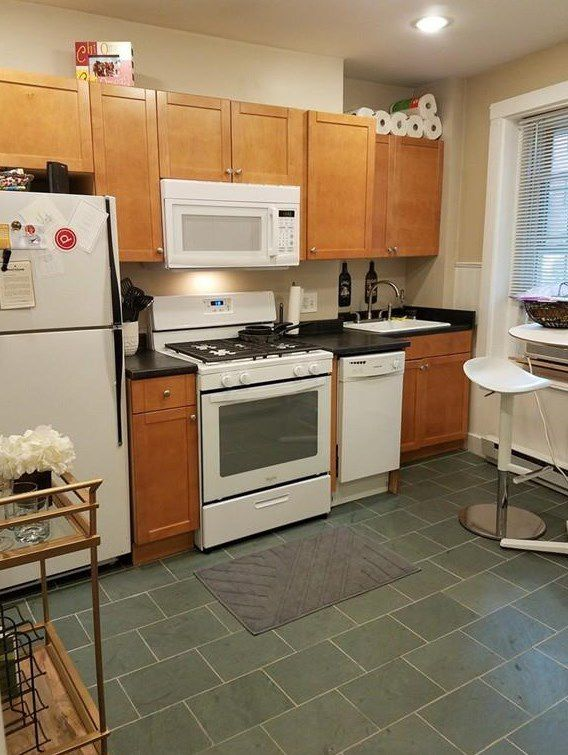 The other side of that kitchen with a counter next to a fridge.