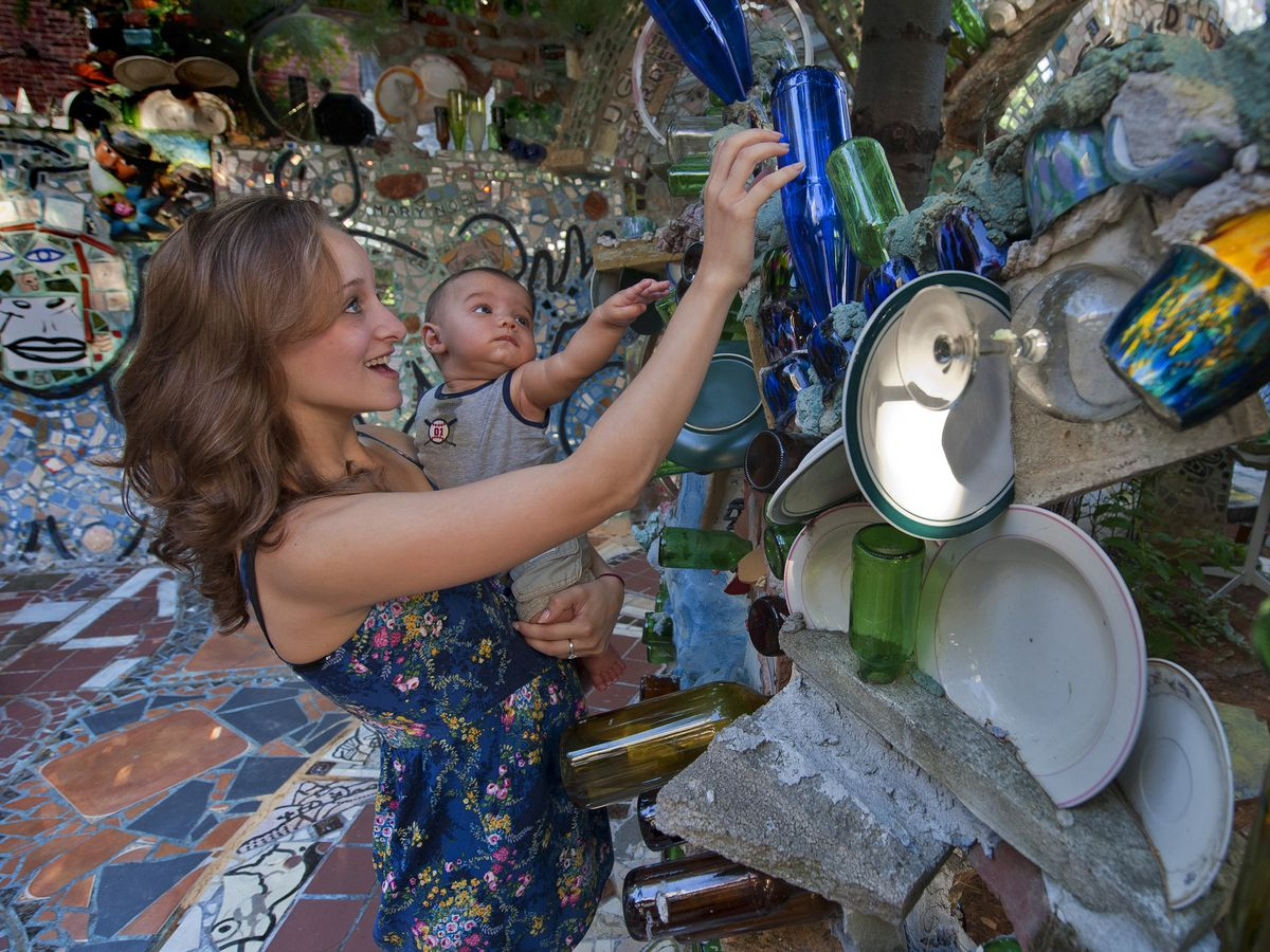A mom and child touch tiles in Philadelphia's Magic Gardens.
