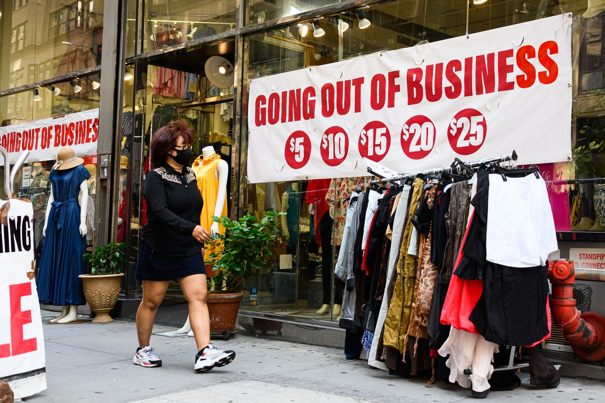 A person wearing a protective face mask walks by a going out of business sign.