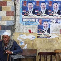 """An Egyptian man smokes at a cafÉ beneath campaign posters for former presidential candidate Hazem Abu Ismail in central Cairo, Egypt, Sunday, April 30, 2012. The Arabic on the poster reads, """"Hazem Salah for Egyptian Presidency."""""""