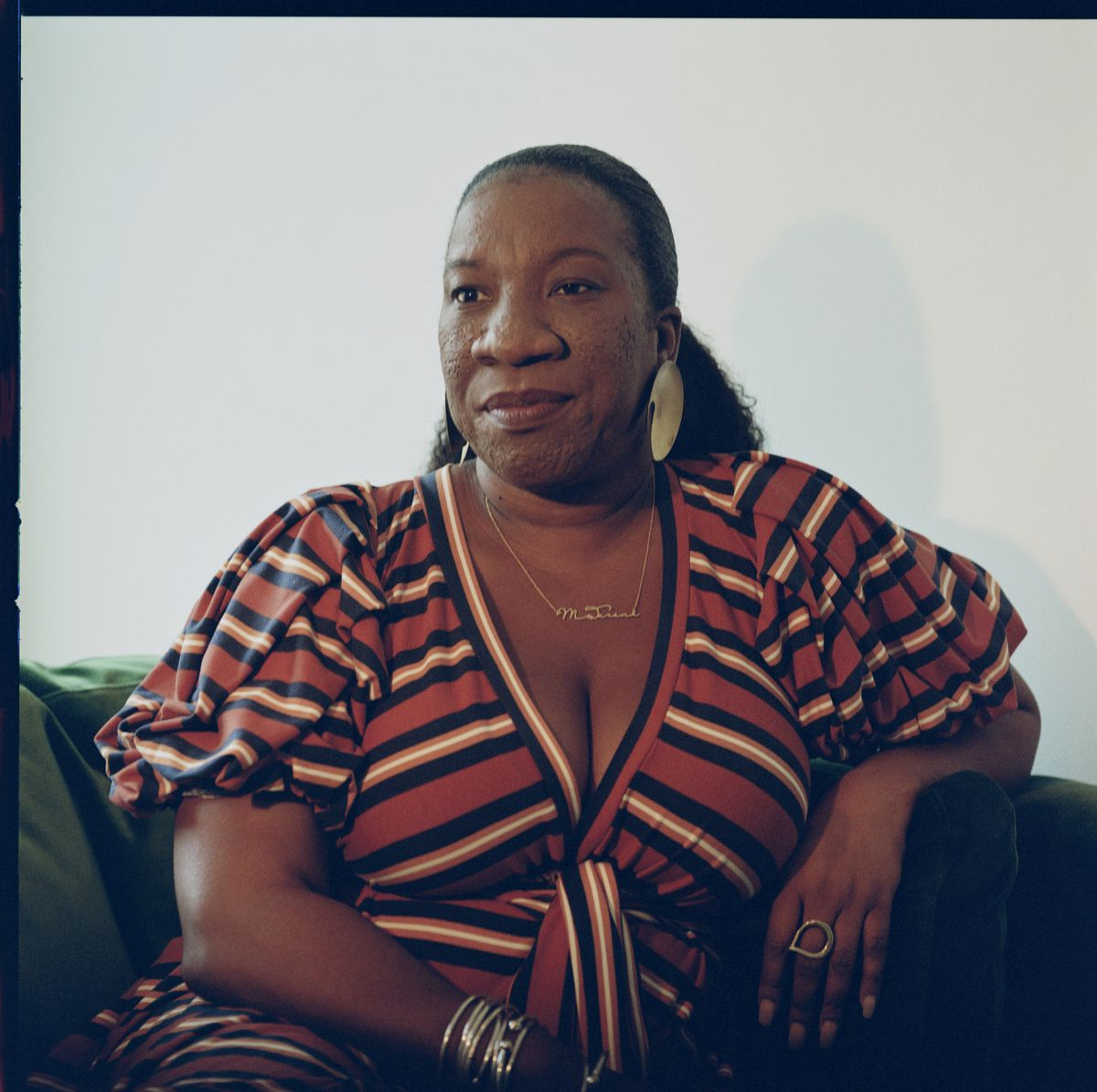 Tarana Burke sitting on a couch in her home.