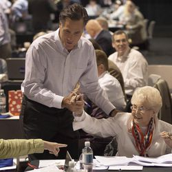 Mitt Romney, left, greets supporters during a phone bank fundraiser, Monday, May 16, 2011, in Las Vegas. The former Massachusetts Gov. and likely GOP presidential contender worked with volunteers to reach out to voters and donors through cell phones and computers in a bid to raise money.