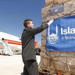 Aaron Meachan, from the LDS Church, hangs a banner on supplies to be flown to Indonesia for earthquake relief.