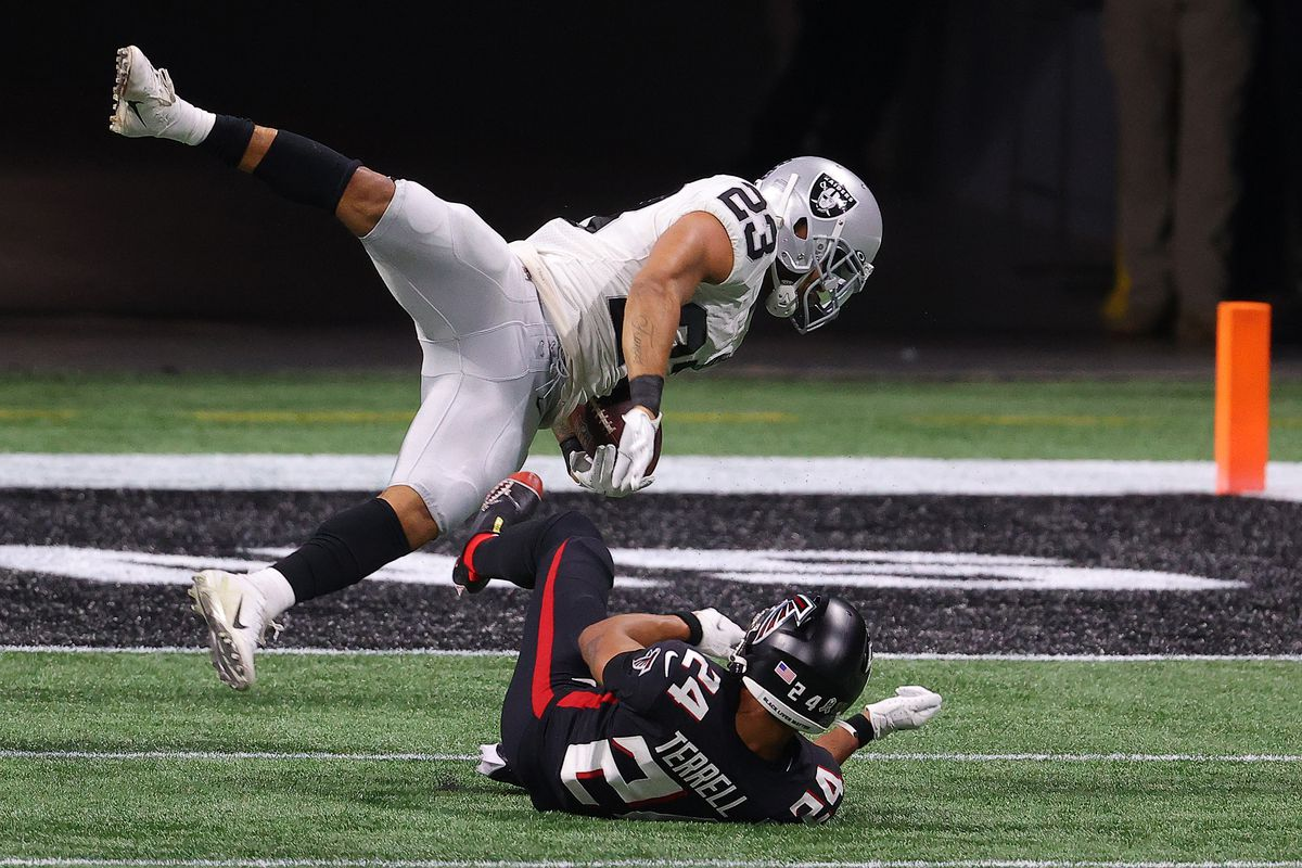 A.J. Terrell #24 of the Atlanta Falcons stops Devontae Booker #23 of the Las Vegas Raiders short of the end zone during their NFL game at Mercedes-Benz Stadium on November 29, 2020 in Atlanta, Georgia.
