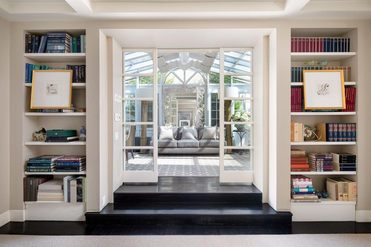 Built-in bookshelves flank sliding glass doors to a bright room.