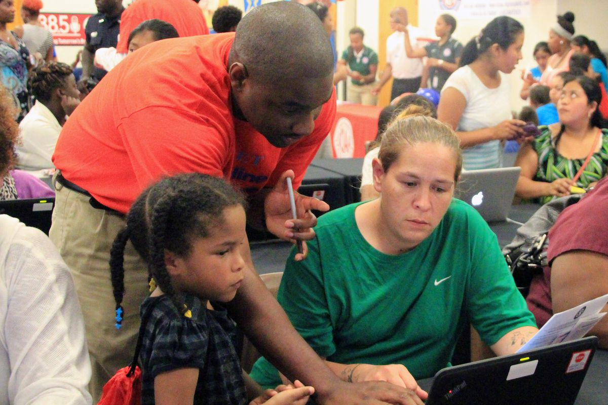 District employee Brandon Pinson works with Samantha Parks at an online registration event last summer.