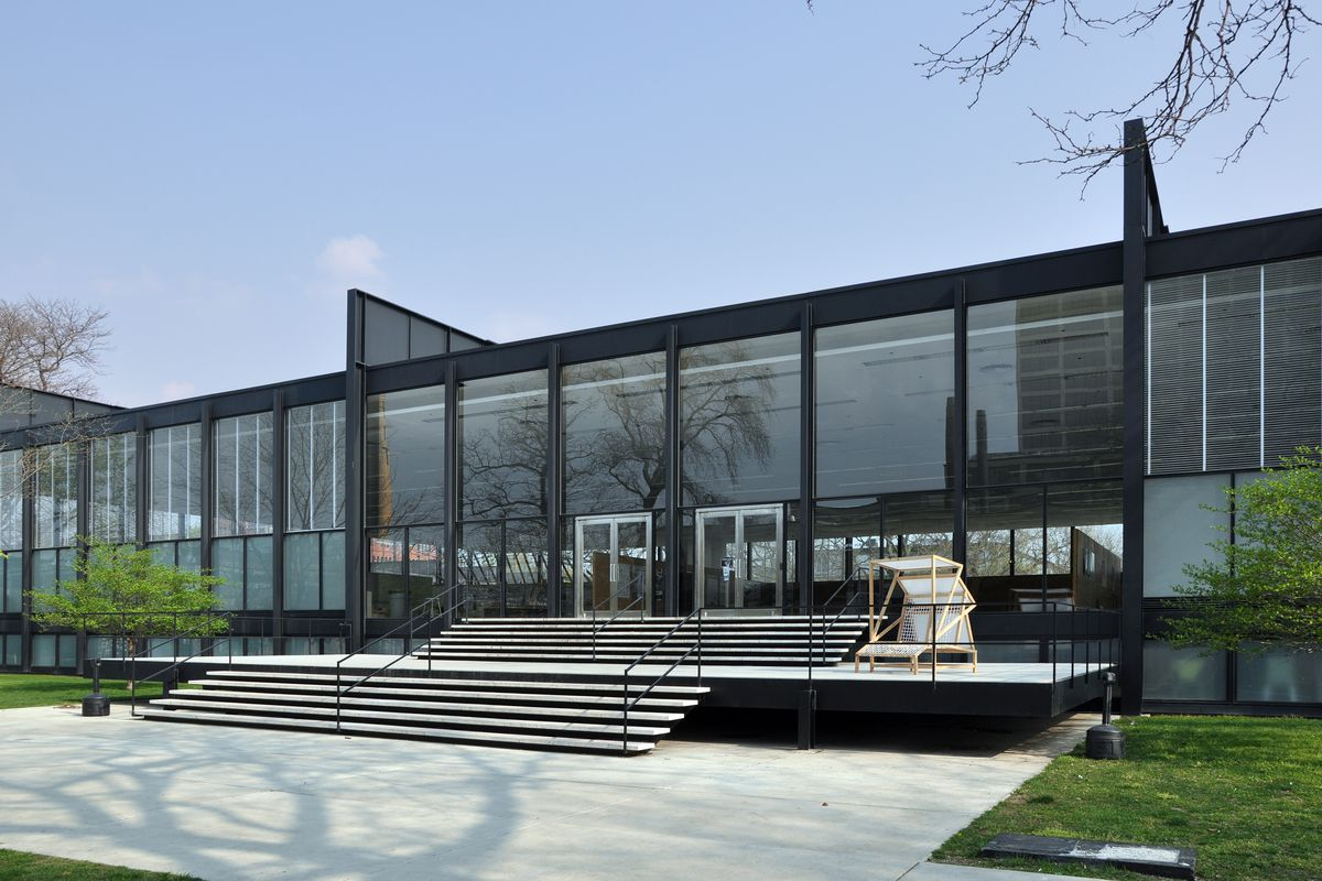A one-story dark steel framed building with large glass windows. Thin and wide steps lead up to the entrance.