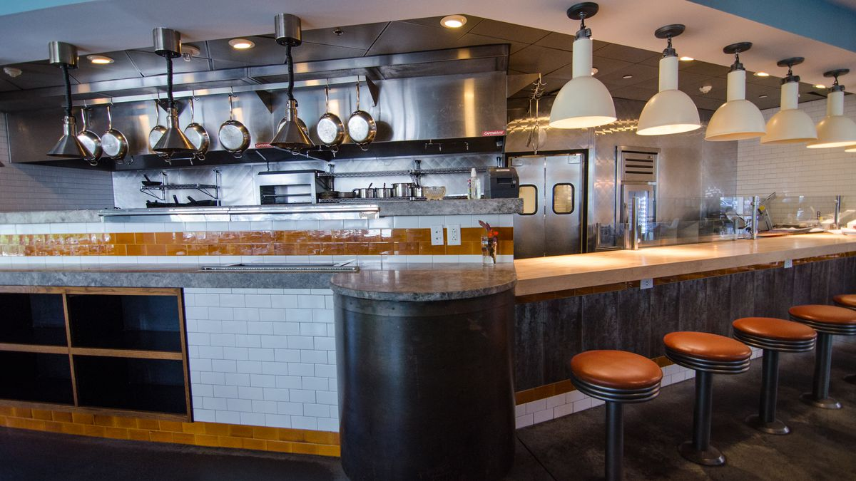 An open kitchen at a restaurant, with some counter seating on reddish stools