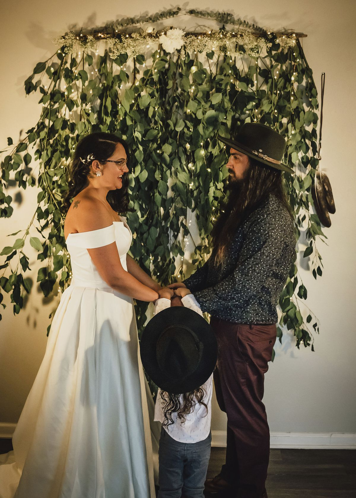 """In this Dec. 2020, photo provided by Kristen Pritchard Photography, Kayleigh and Cody Cousins hold hands during their wedding ceremony, accompanied by their son, River, at home in San Diego, Calif. They initially planned an April 2020 wedding, postponed it after the pandemic took hold, rescheduled it for December, then had to shift gears again when a new lockdown was imposed. """"That was devastating,"""" said Kayleigh. """"We said, 'Let's just do it on Zoom.'"""""""