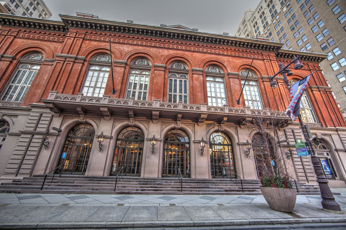 The exterior of the Academy of Music in Philadelphia. The top of the building is red brick and the bottom is brown brick. There are arched windows and stairs leading up to the entrance.