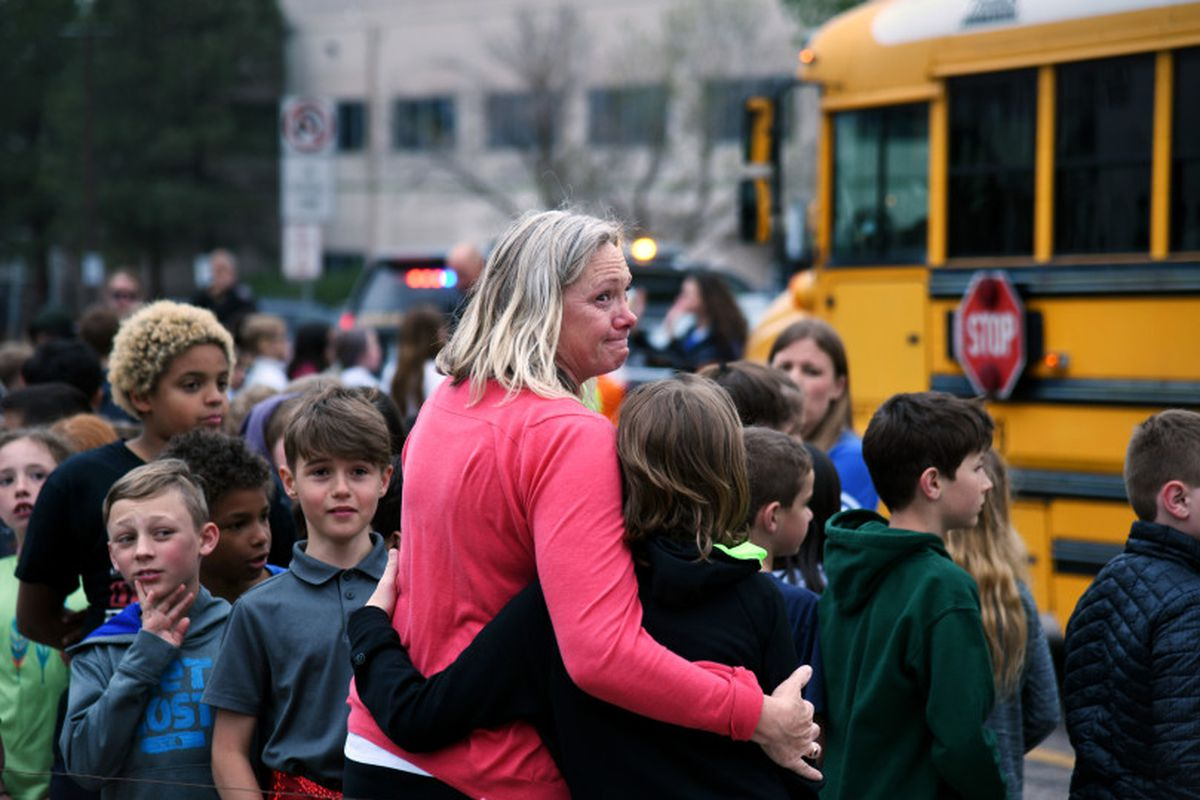 Melanie Fitzroy, an AM Elementary EA, embraces a child as students wait to be escorted to buses as they are evacuated from STEM School Highlands Ranch after a school shooting.