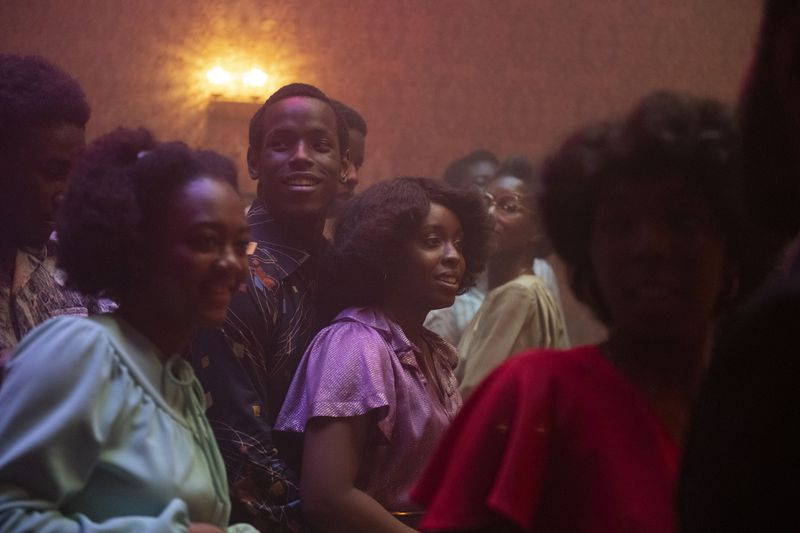 Un groupe de jeunes dansent dans une pièce faiblement éclairée.