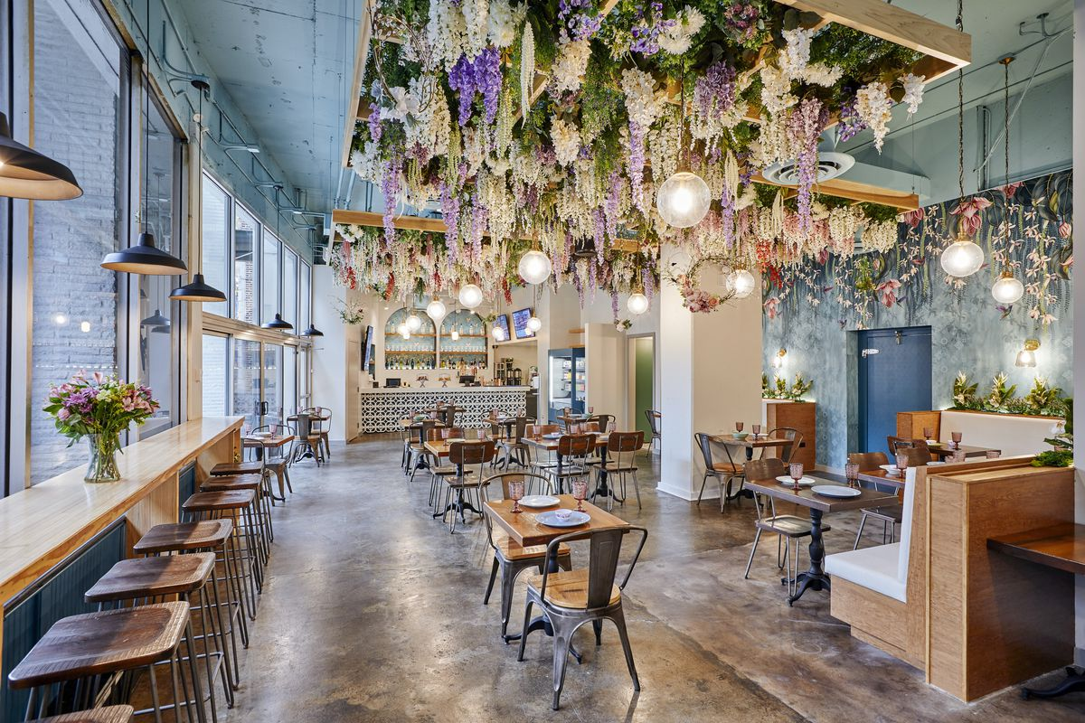 A bright dining room with a hanging garden of pink, purple, and white flowers over wooden tables and chairs.