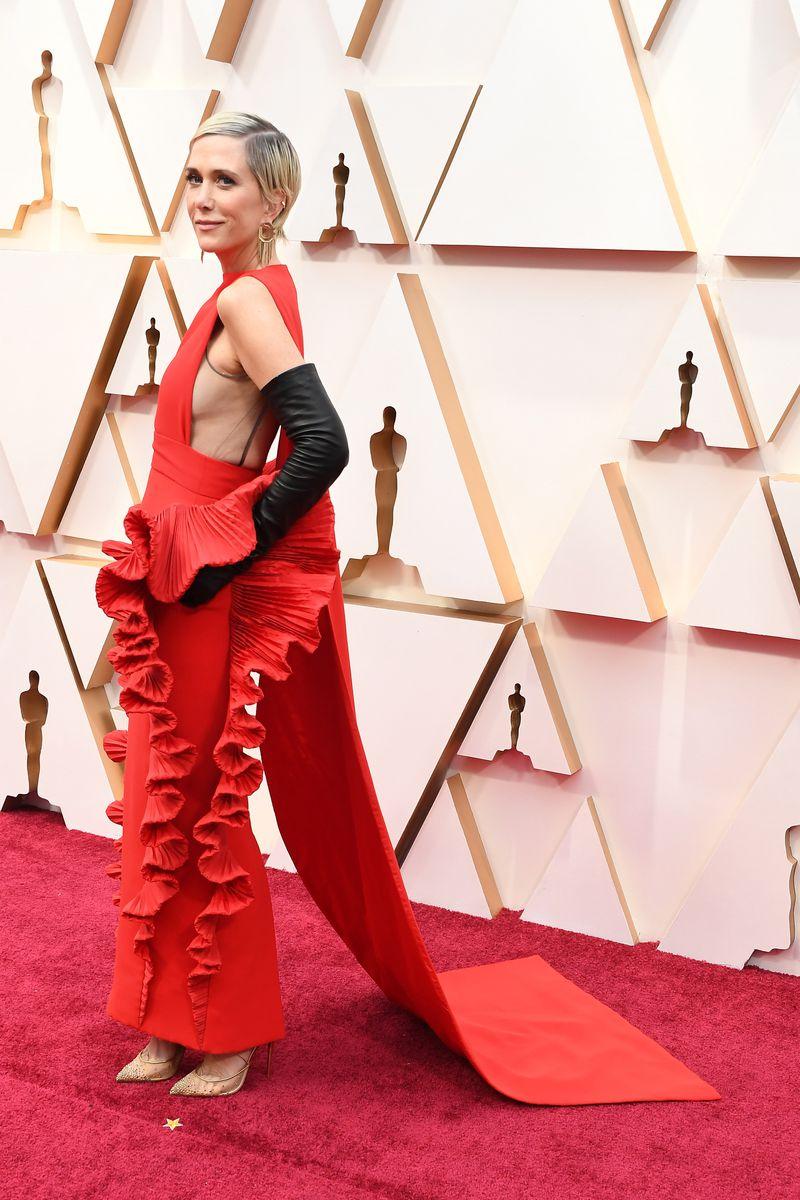 Kristen Wiig poses on the Oscars red carpet.
