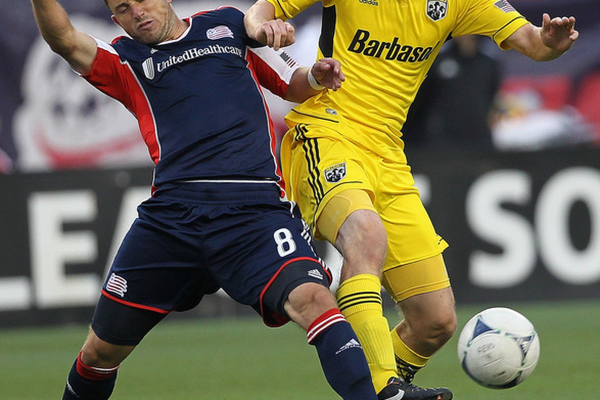 FOXBORO, MA - JUNE 16:  Eddie Gaven #12 of the Columbus Crew battles Chris Tierney #8 of the New England Revolution during a game at Gillette Stadium on June 16, 2012 in Foxboro, Massachusetts. (Photo by Jim Rogash/Getty Images)