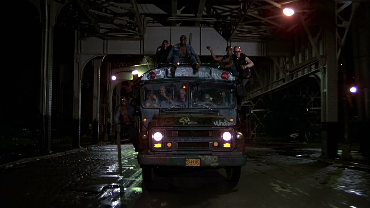The Warriors ride and hang off of a bus on a bridge