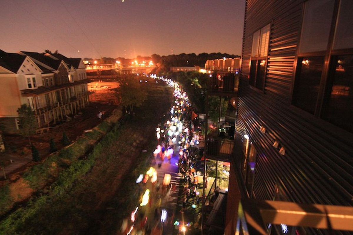 A row of townhomes being built at left and the steel building at right, with a lantern parade below.